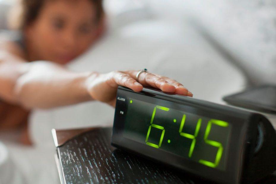 ผู้หญิงเอื้อมมือไปกดปุ่มเลื่อนบนนาฬิกาปลุกดิจิตอล