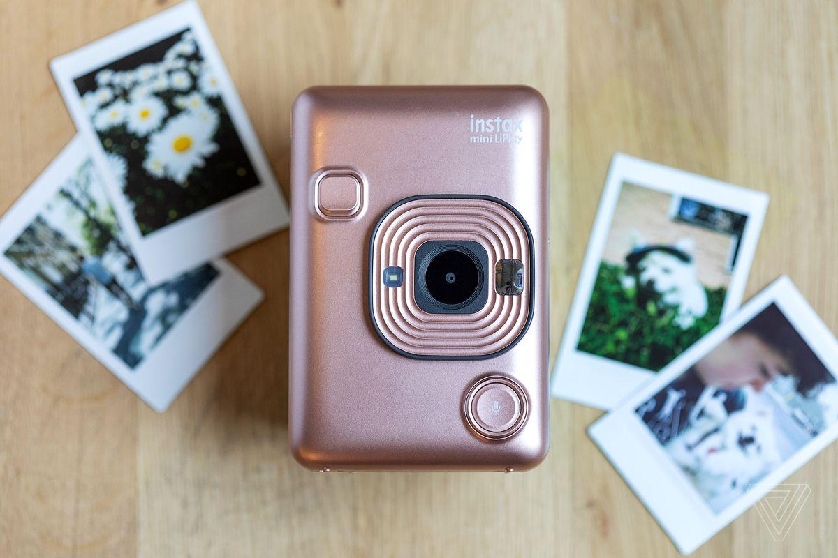 กล้องโพลารอยด์บนโต๊ะที่ล้อมรอบด้วยภาพถ่ายโพลารอยด์
