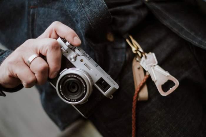 ผู้หญิงกำลังถ่ายรูปด้วยกล้องคอมแพค