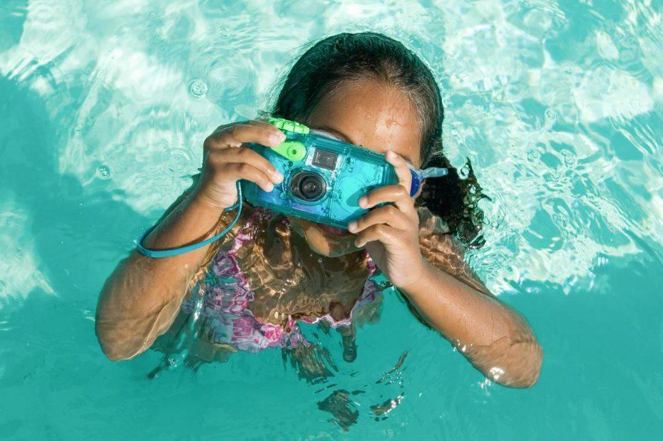เด็กกำลังถ่ายรูปด้วยกล้องใต้น้ำในสระว่ายน้ำ