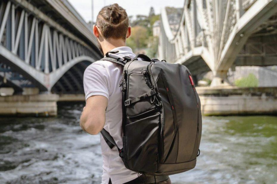 ชายหนุ่มสะพายกระเป๋าเป้ขณะเดินริมแม่น้ำ
